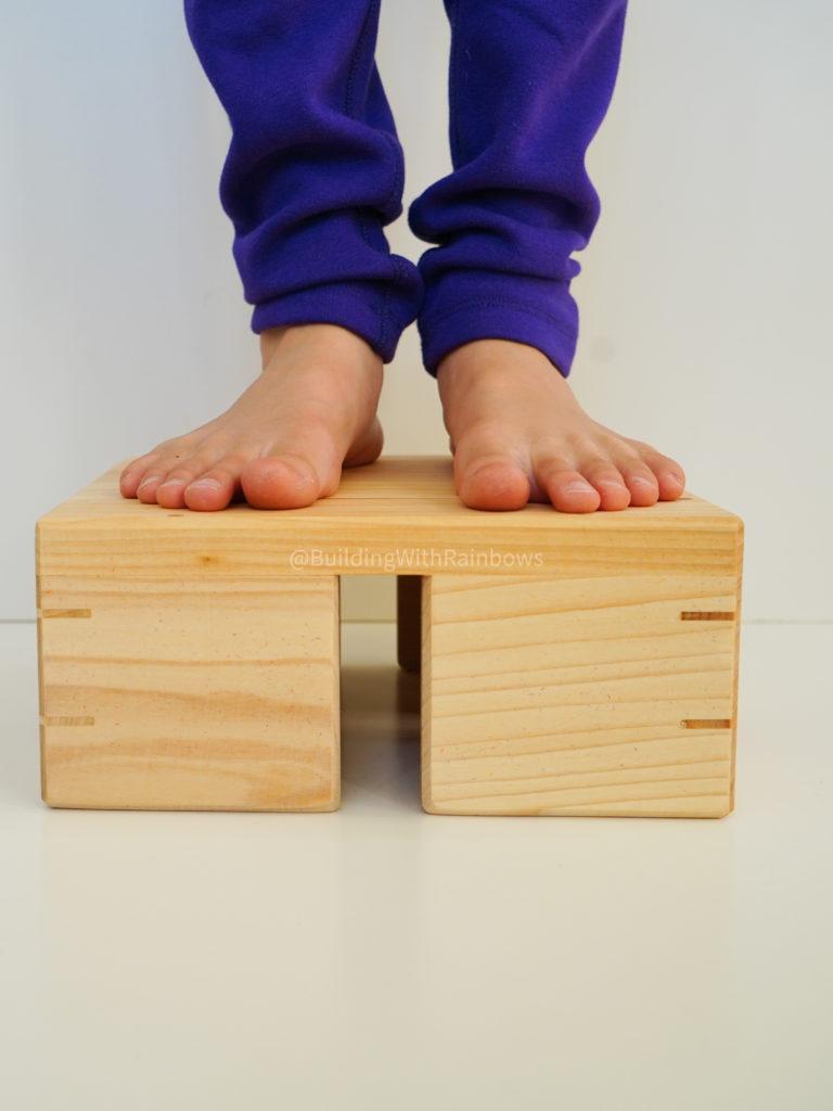 child standing on bauspiel color tile box